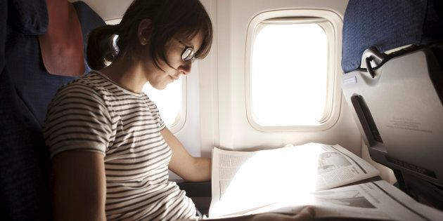 Woman reading newspaper in aeroplane, close-up