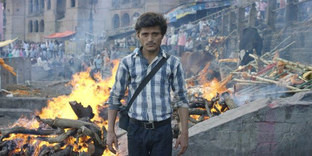 'Nadi the death photographer' stands afront the burning ghats of Varanasi,