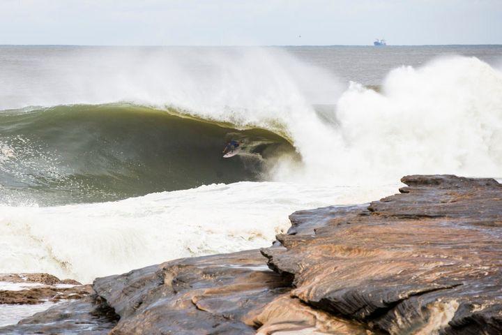 Blake Thornton on a wave breaking close to rocks.