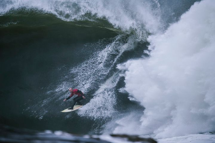 Justen Allport is dwarfed by a wave.