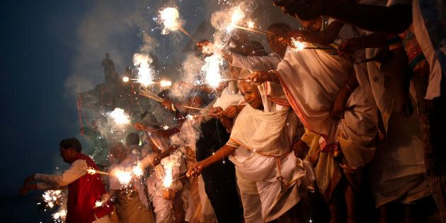 Widows light sparklers after offering prayers as part of Diwali
