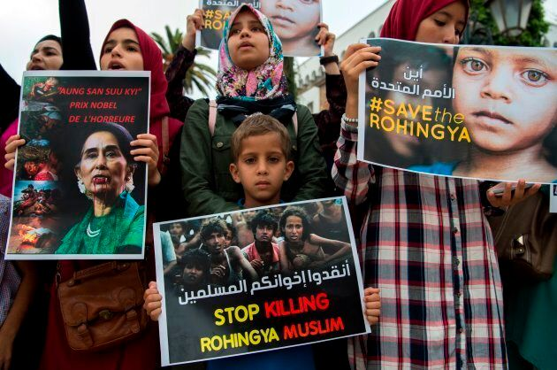 Moroccans, some of them holding placards depicting Nobel Peace Prize winner Aung San Suu Kyi, take part...