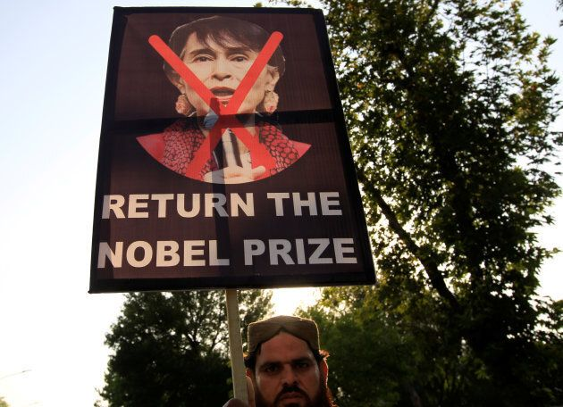 A demonstrator holds a placard during a protest against Myanmar's persecution of Rohingya Muslims in...
