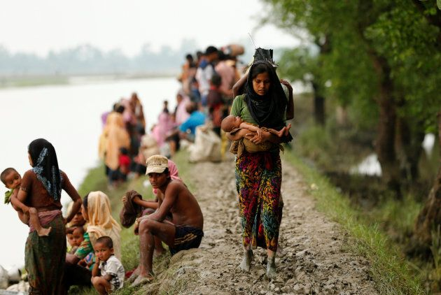 A Rohingya refugee woman with her child walks on the muddy path after crossing the Bangladesh-Myanmar...