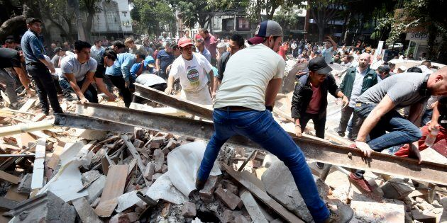 People remove debris of a building which collapsed after a quake rattled Mexico