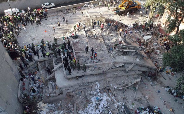 Rescuers look for survivors in a multistory building flattened by a powerful quake in Mexico