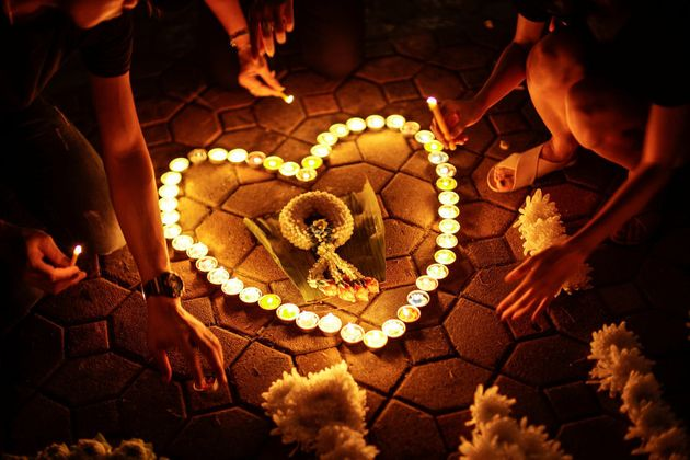 Mourners light up candles outside of the Grand Palace to pay respects to the