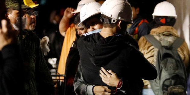 Workers hug during the search for students at Enrique Rebsamen