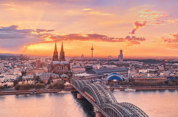 A glowing Cologne at sunset, with the Cathedral (Dom), old town, the Musical Dome and the Rhine River in view.