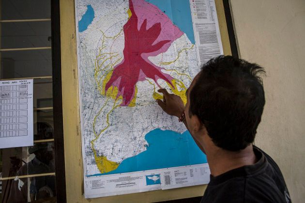 A man looks a map of the danger zones at the Mount Agung monitoring station in the Karangasem regency...