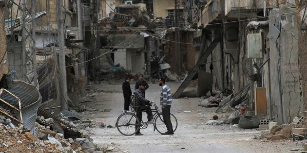 Men chat near buildings damaged by what activists said was shelling by forces loyal to Syria's President Bashar al-Assad in Daraya, near Damascus February 2, 2014. Picture taken February 2, 2014.REUTERS/Omar Abu Bakr (SYRIA - Tags: POLITICS CIVIL UNREST CONFLICT)