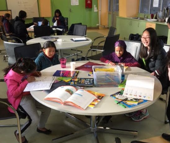 A high school student helping out at Homework Club