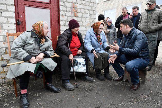 Ukrainian Prime Minister Volodymyr Groysman meets with local residents at a collection point for