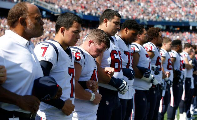 The Houston Texans stand and link arms during the national anthem before the game against the New England