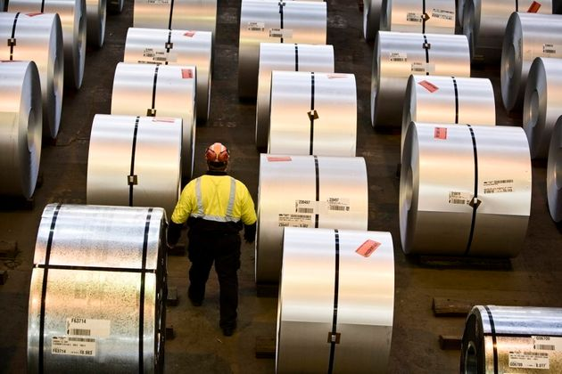 A worker walks among the steel coils produced at Port