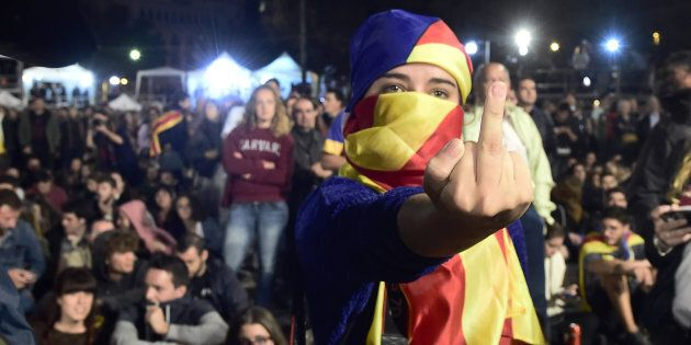 A woman, whose face is covered with a Catalan pro-independence flag, gestures as people sit on Plaza...