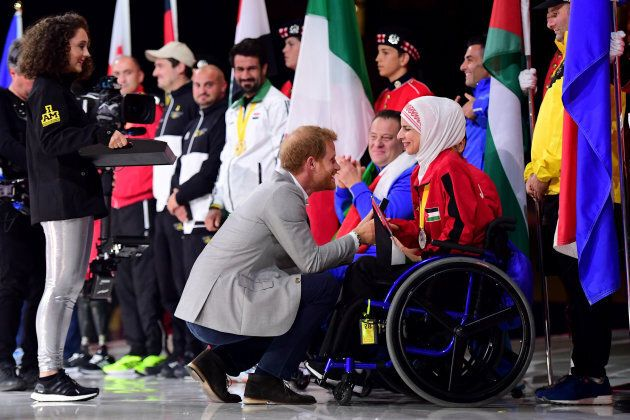 Prince Harry shakes hands with flag bearer Ulfat Al-Zwiri of Jordan during the closing ceremony of the...