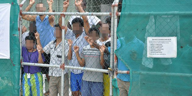 Asylum-seekers look through a fence at the Manus Island detention centre in Papua New Guinea March 21,...