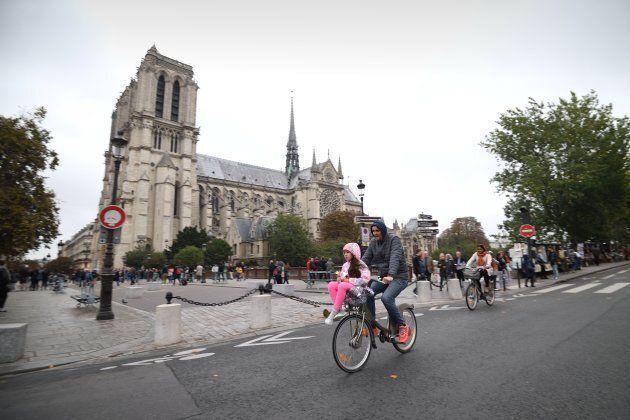 A cyclist rides past Notre Dame