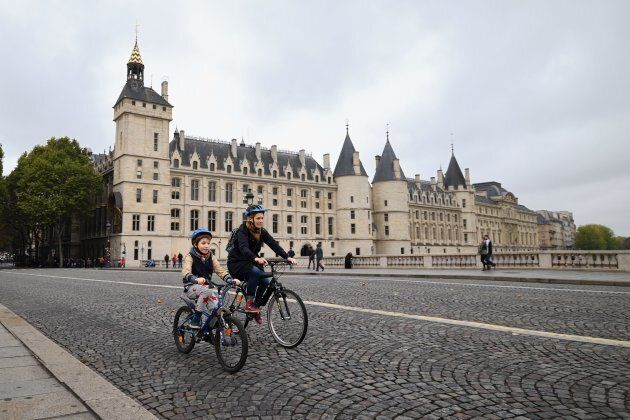 A cyclist rides past the 'Conciergerie', a former prison and royal