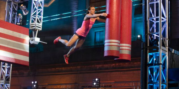 An American Ninja Warrior contestant jumps and