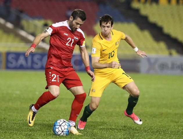 Faced Youssef of Syria is pressured by Robbie Kruse during the 2018 FIFA World Cup Asian