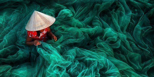 In a small village in southern Vietnam near Phan Rang a woman wearing a typical cone hat is creating a fishing net in their traditional manner The manufacturing of handmade nets is still a typical Vietnamese activity for women which they carry on while their husbands are out fishing