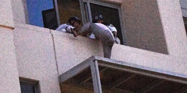 The man remained on the roof of an awning 26 floors high for more than half a