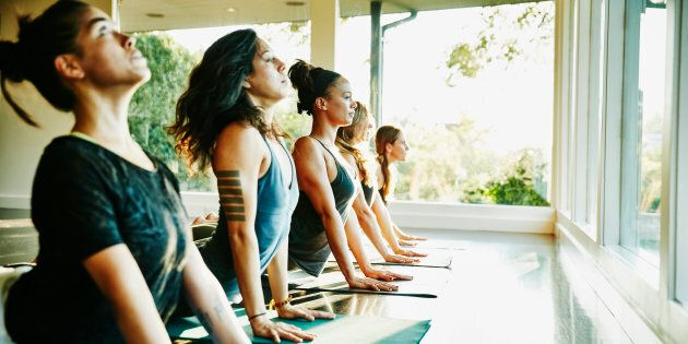 Women practicing yoga in studio in cobra pose