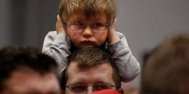 A child covers his ears before Republican presidential nominee Donald Trump appears at a campaign rally...