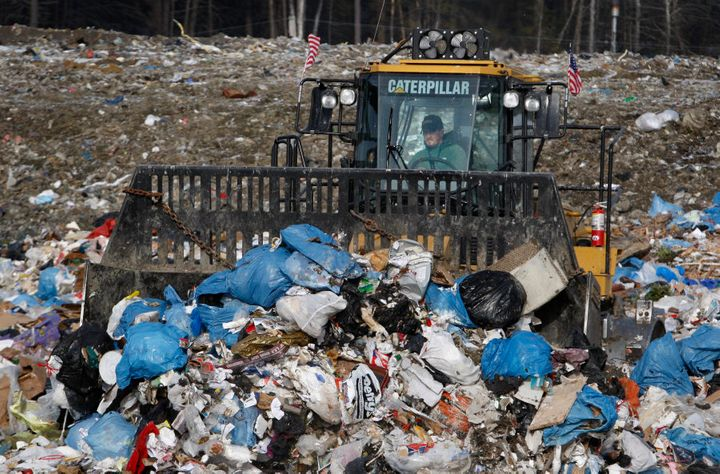 A bulldozer operator plows trash at the town landfill, Wednesday in Bath, Maine.
