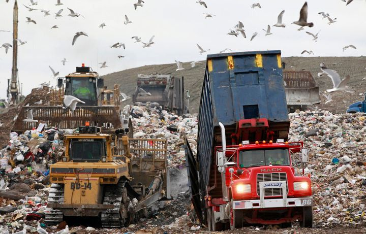 A garbage truck empties its load as bulldozers process the waste at the Central Landfill, in Johnston, Rhode Island, U.S.A.