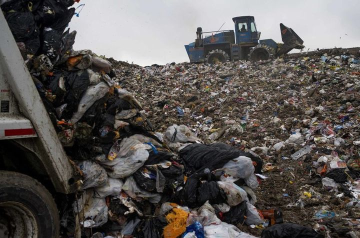 A compactor packs down trash to be covered with fresh dirt at the Defiance County Landfill in Defiance, Ohio, U.S.A.