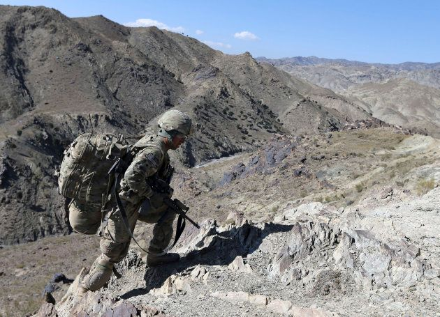 A U.S soldier climbs a hill with a heavy rucksack In Afghanistan in
