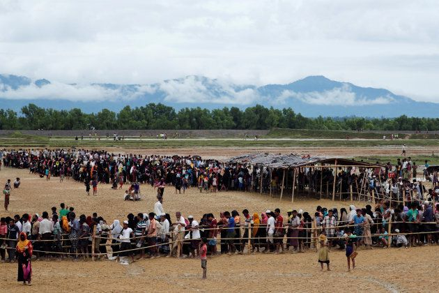 Rohingya refugees line up to receive food at a camp near Teknaf,