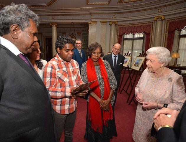 Queen Elizabeth II and the Duke of Edinburgh talk with Kevin Namajtira (left) the grandson and Lenie...