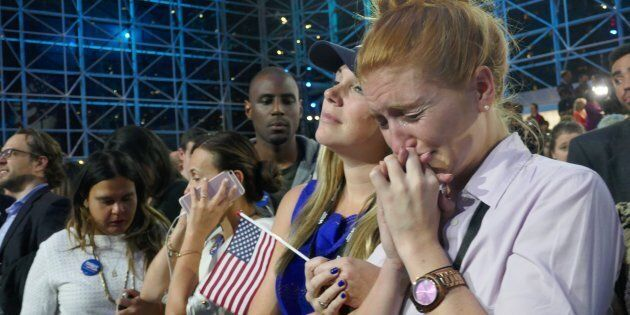 Democratic Party's presidential nominee Hillary Clinton's supporters show their sorrow as the results...