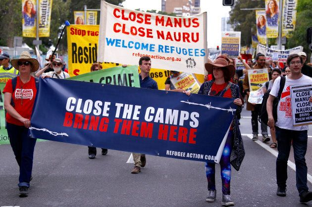 Refugee advocates hold placards as protest against the treatment of asylum-seekers in detention centres, in Sydney on October 15