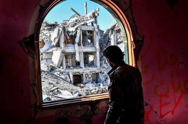 A member of the Syrian Democratic Forces looks out from a building at the frontline in Raqa on October 16, 2017.