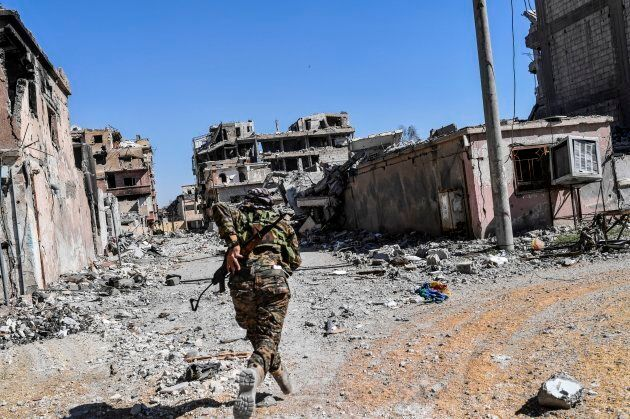 A member of the Syrian Democratic Forces (SDF) runs as he tries to take a cover near Raqa's stadium as...