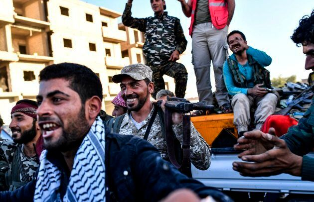 Members of the Syrian Democratic Forces (SDF) celebrate at the frontline in the Islamic State (IS) group...