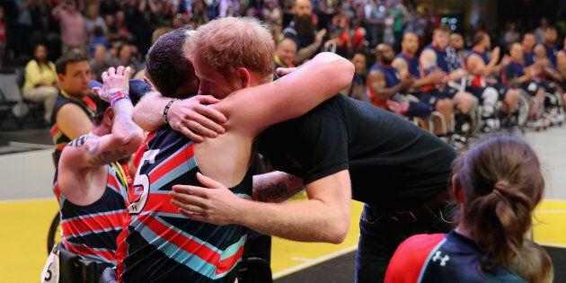 Prince Harry hugs competitors and presents medals during the wheelchair basketball on the final day of...