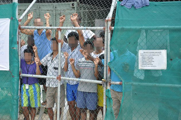 Asylum-seekers look through a fence at the Manus Island detention centre in Papua New
