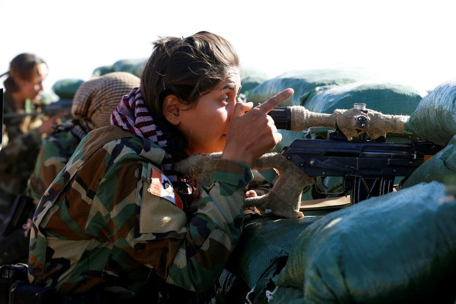 An Iranian-Kurdish female fighter takes position during a battle against Islamic State militants in Bashiqa...