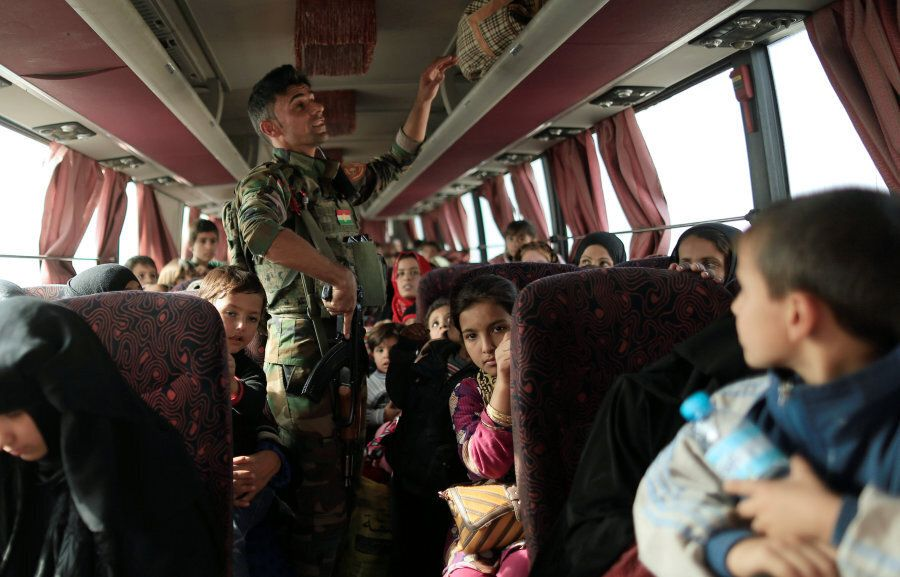A Peshmerga soldier checks the bag compartment of people who are fleeing the fighting between Islamic...