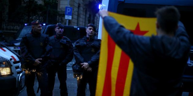 A demonstrator holds up an Estelada (Catalan separatist flag) during a gathering in front of the Spanish...