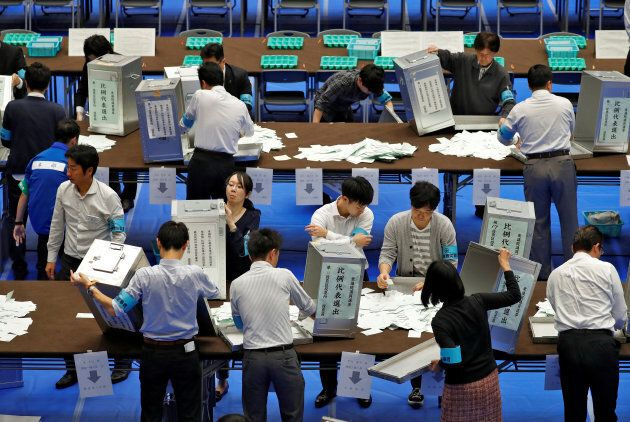 Election officials open ballot boxes to count votes after Japan's lower house election.