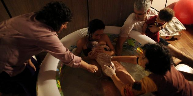 Mother Manuela Mitre gives birth to second child Gael while lying in a pool of water, at her home in...