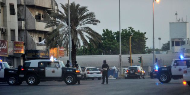 Saudi policemen stand guard at the site where a suicide bomber blew himself up in the near the American...