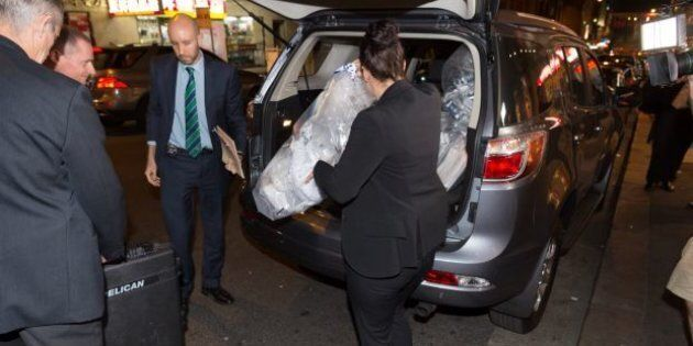 AFP officers load bags of shredded documents into a van during a raid on AWU offices on